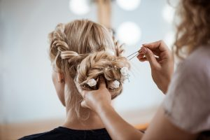 Female hairdresser making hairstyle to beautiful blonde girl in beauty salon. Copy space.
